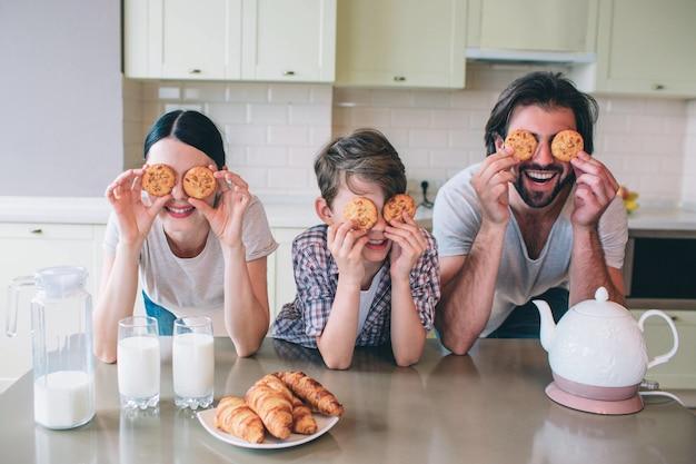 행복한 가족이 롤 놀고있다. 그들은 눈에 웃으며 웃었다. 가족은 테이블에 기대어 있습니다. 주전자, 우유, 크로 이산이 있습니다.