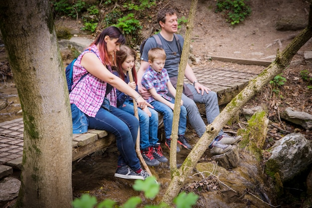 Happy family are sitting on a wooden bridge in the middle of forest
