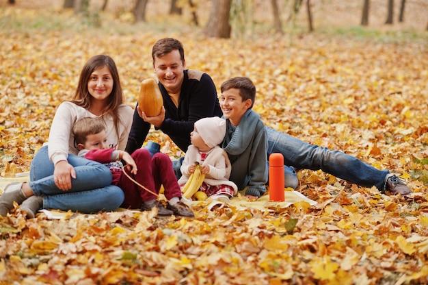 秋の幸せな家族は公園を去ります。 3人の子供。