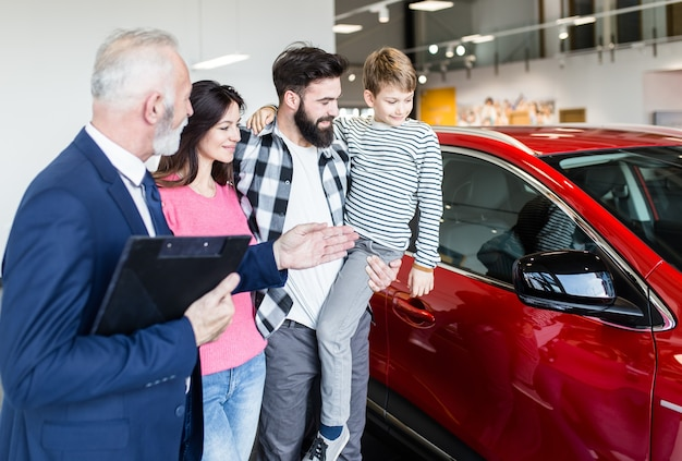 Счастливая семья в автосалоне, выбирая новую для покупки.