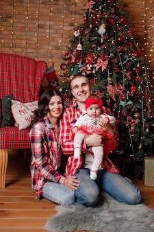リビングルームの家で飾られた木の近くに一緒に座っているクリスマスイブの幸せな家族父母と女の赤ちゃん新年の休日を祝うコンセプト