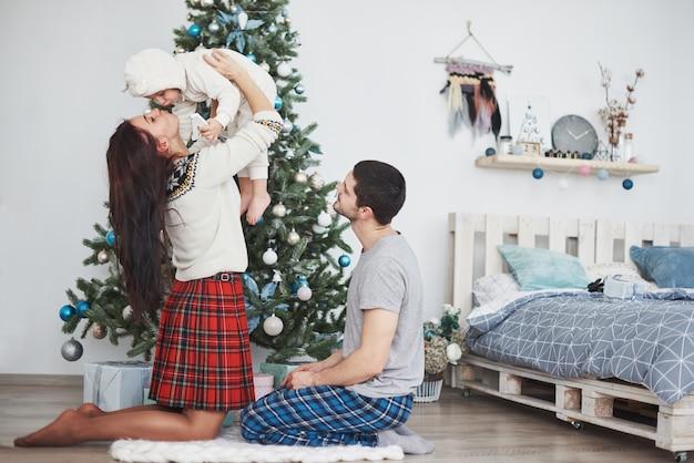 전나무 나무 근처에 함께 선물을 열어 아침에 크리스마스에 행복 한 가족.