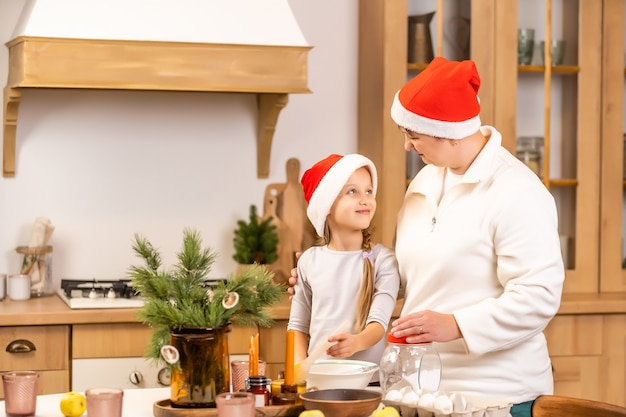 Счастливая семья на рождество. мать и дочь весело дома