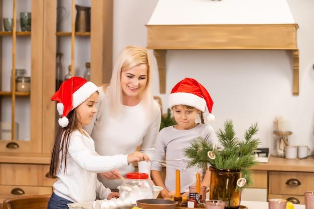 Счастливая семья на рождество. мать и дочери веселятся дома