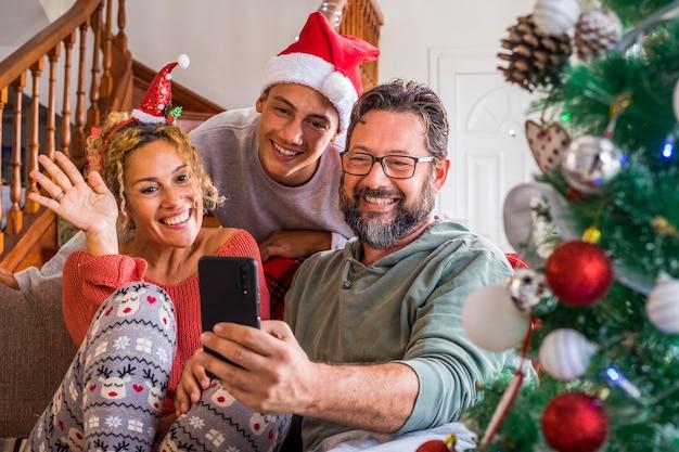 クリスマスイブの日の家で幸せな家族は、友人や両親とのビデオ電話をお楽しみください