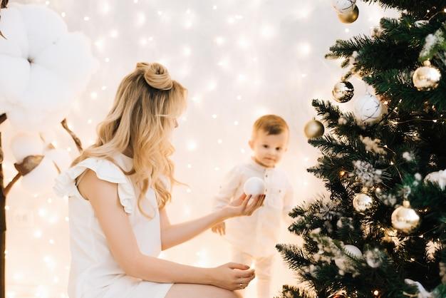 크리스마스 트리와 선물 집 인테리어에 행복 한 가족. 크리스마스 장식 중 그녀의 아이와 아름 다운 어머니.