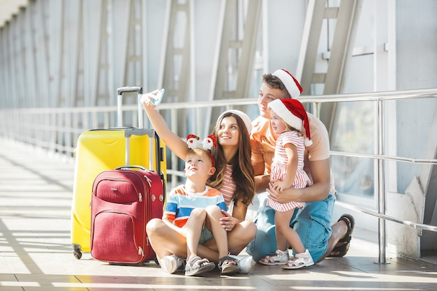 Счастливая семья в аэропорту с багажом