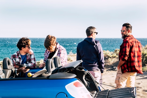 Счастливая семья на пляже с машиной - два человека смотрят на море и разговаривают, а два подростка вместе смеются и используют свои телефоны