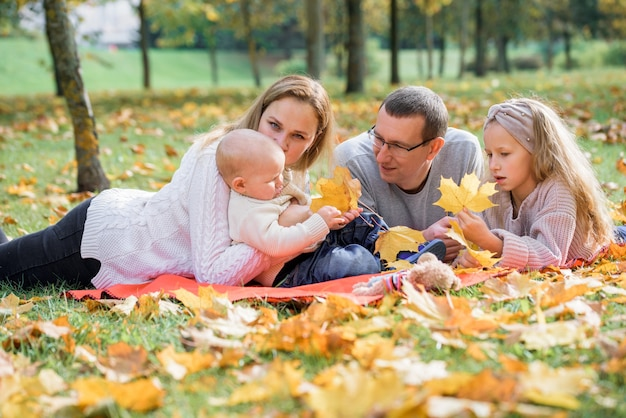 Happy family on autumn picnic in park.