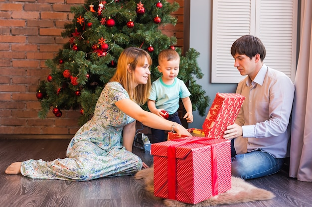 Happy family, baby boy holding christmas gift