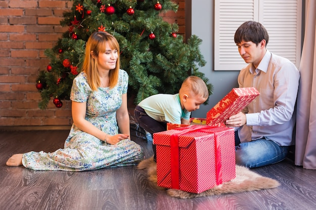 Happy family, baby boy opens christmas gift