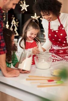 Счастливая семья, выпекающая печенье на рождество