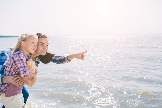 Happy family on the beach. people having fun on summer vacation. mother and child against blue sea and sky background. holiday travel concept