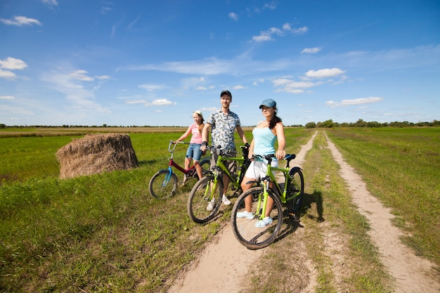 Happy family on bikes standing in a field in summer