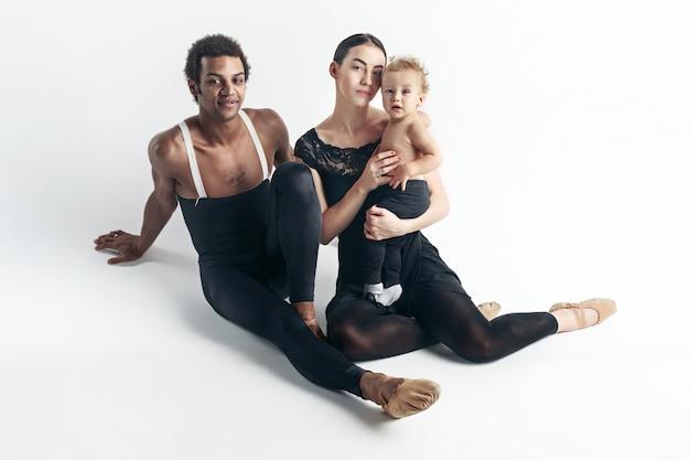 Una famiglia felice in abiti neri, seduta sul pavimento