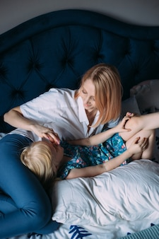 Happy family of blonde mom and daughter are playing and having fun in bed.