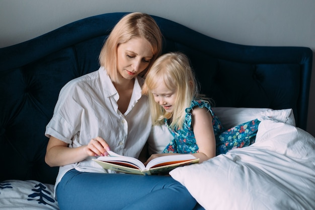 Happy family of blonde mom and daughter are reading a book in bed.