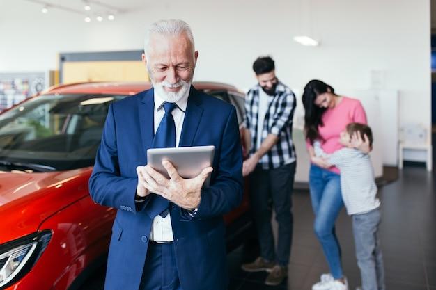 Счастливая семья покупает новую машину в автосалоне.