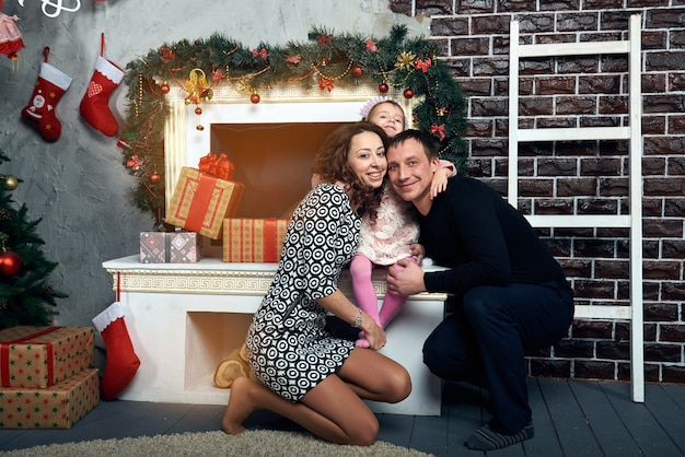 Happy family by the fireplace for the winter holidays. christmas eve and new year's eve.