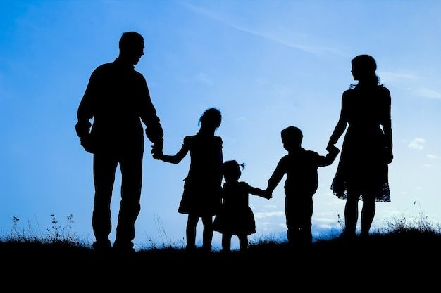 Happy family by the sea on nature silhouette