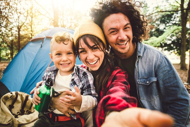 Happy family camping in the forest taking selfie portrait together - mother, father and son having fun trekking in the nature sitting in front of the tent - family, nature and trekking concept