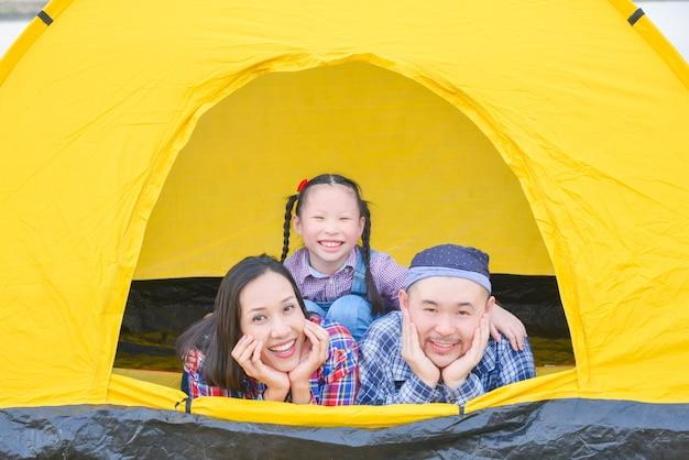 휴가를 즐기는 행복한 가족 아버지 어머니와 딸이 함께 텐트에 누워 웃고