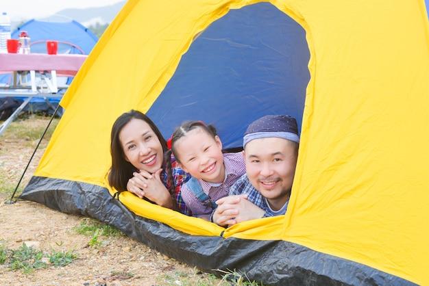 휴가에 캠핑하는 행복한 가족아버지 어머니와 딸이 함께 텐트에 누워 미소를 짓고 있습니다.