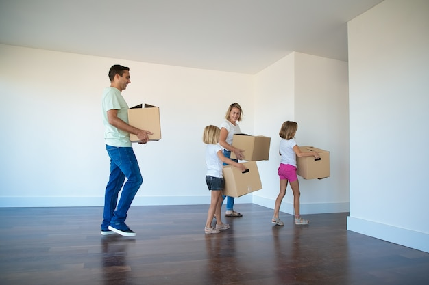 Happy family carrying cardboard boxes from empty room