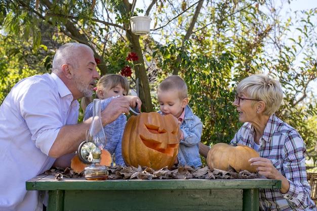 Счастливая семья, вырезая тыкву вместе и наслаждаясь днем вместе