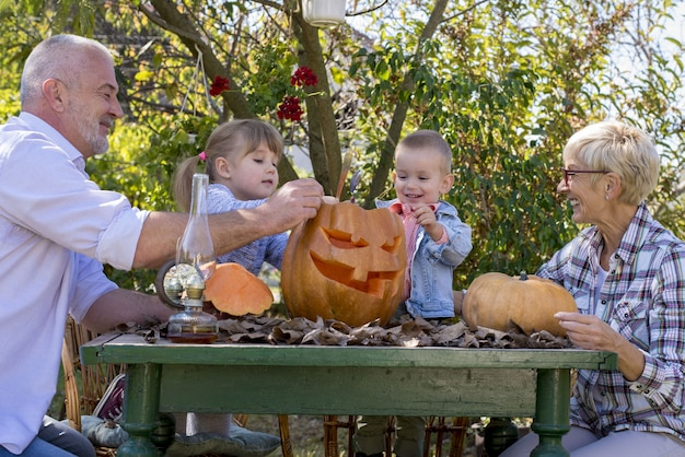 Happy family carving pumpkin together and enjoying a day together