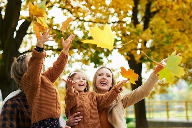 Famiglia felice che cattura foglie autunnali