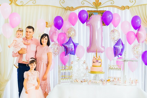 幸せな家族は美しい休日の雰囲気の中で子供の誕生日を祝います