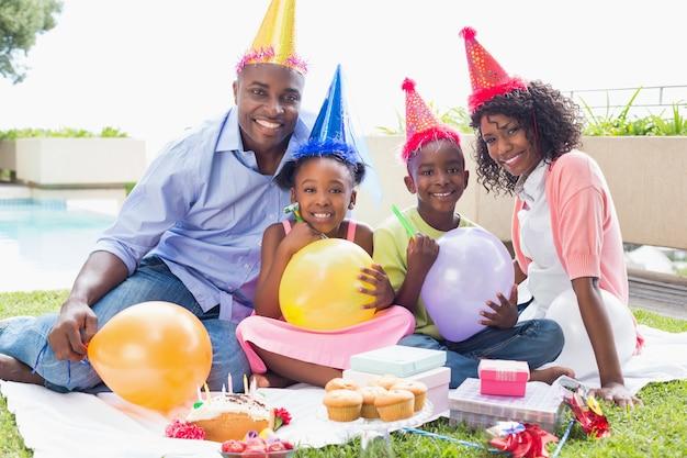 화창한 날에 정원에서 함께 생일을 축하하는 행복한 가족