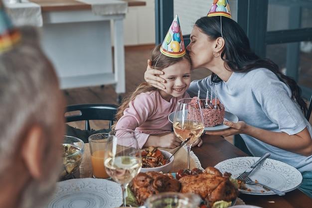 自宅の食卓に座って小さな女の子の誕生日を祝う幸せな家族
