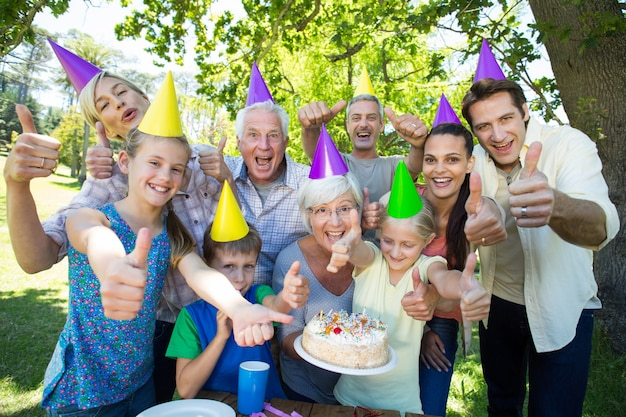 Happy family celebrating a birthday with thumbs up