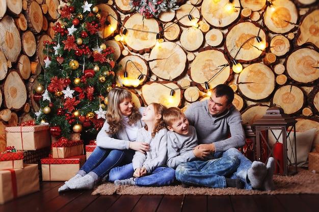あなたの家の美しいクリスマスツリーでクリスマスと新年を祝う幸せな家族。