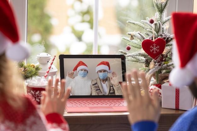 検疫のビデオチャットでオンラインでクリスマス休暇を祝う幸せな家族。封鎖の家の概念。パンデミックコロナウイルスcovid19中のクリスマスパーティー