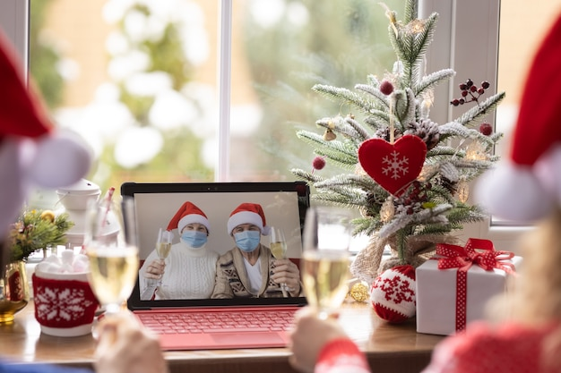 Happy family celebrating christmas holiday online by video chat in quarantine. lockdown stay home concept. xmas party during pandemic coronavirus covid 19