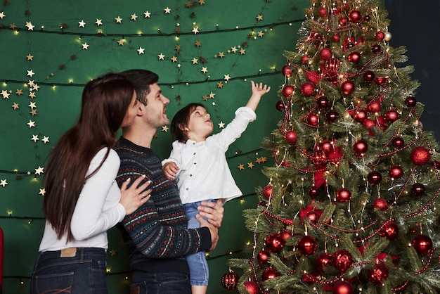 Happy family celebrating new year and standing near christmas tree.