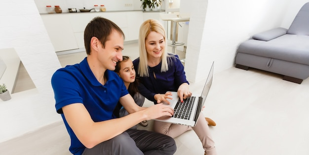 Happy family chatting online using laptop while sitting with baby at home.