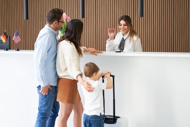 Счастливая семья, заселяющаяся в отель