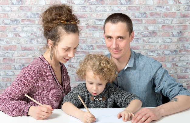 Happy family, child, father and mother drawing