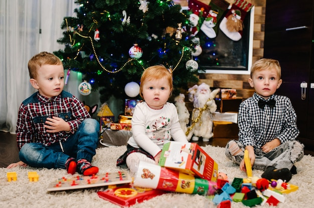 幸せな家族:子供、子供、娘と息子、男の子と女の子はクリスマスツリーと暖炉の近くで贈り物を開梱します。新年のコンセプト。メリークリスマス。