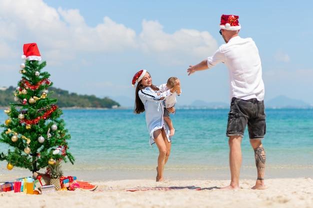 幸せな家族。クリスマスのカップルと子供時代。海の背景。