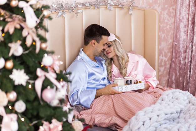 Happy family on christmas morning in bed in pajamas