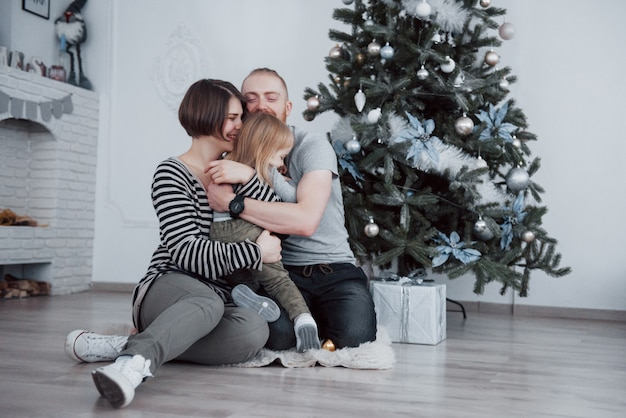 Happy family at christmas in morning opening gifts together near the fir tree. the concept of family happiness and well-being