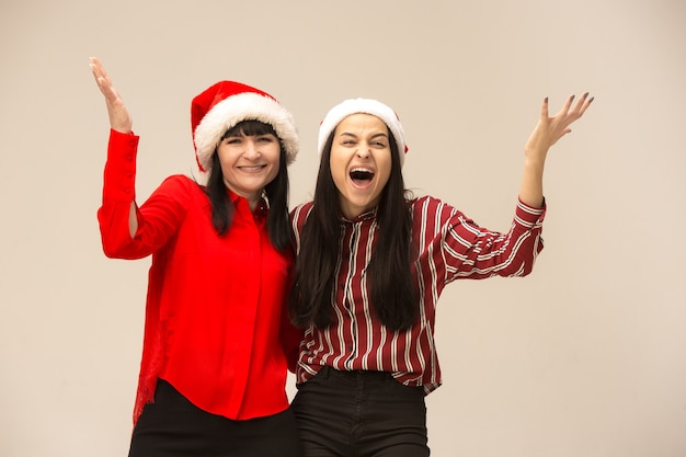 Happy family in christmas sweater posing. enjoying love hugs, holidays people. mom and doughter on a gray background in the studio