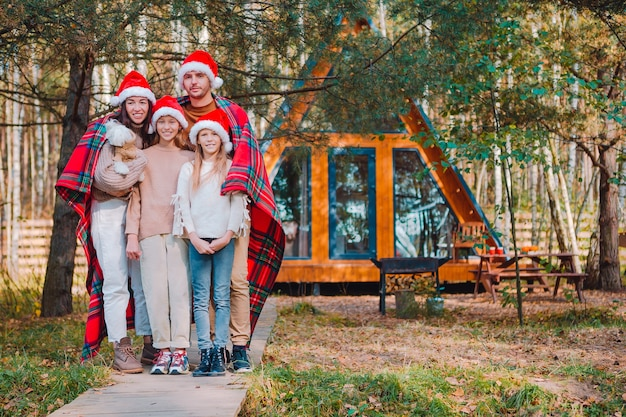 Happy family on christmas vacation. parent with kids wrapped in a blanket