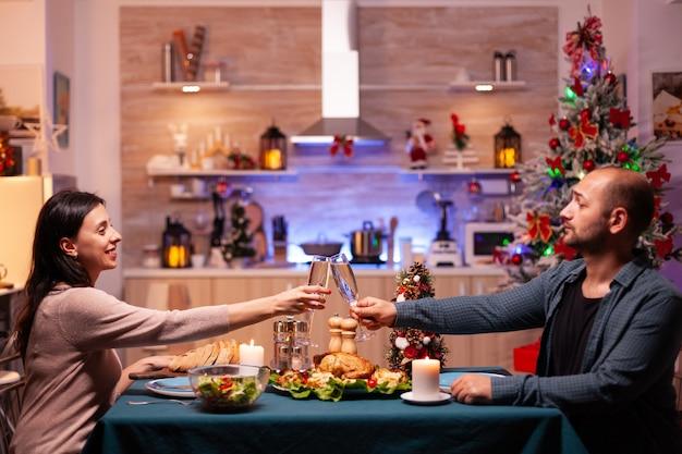Famiglia felice che si scontra con un bicchiere di vino seduto al tavolo da pranzo