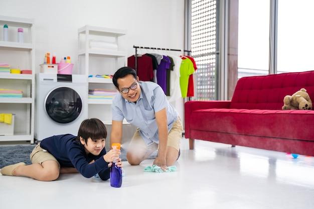 Счастливая семья убирает комнату. азиатские отец и сын делают уборку в доме. молодой человек и девочка вытирают пыль, моют пол полотенцем и спреем в гостиной.
